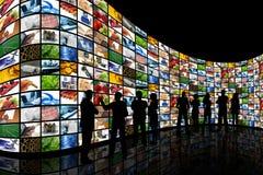 La gente che esamina parete degli schermi Fotografia Stock