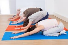 La gente che esegue yoga alla palestra Immagini Stock Libere da Diritti