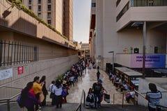 La gente che fa la coda lungo il lato di Sheraton Lima Hotel e di Convention Center in Lima Peru immagini stock