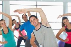 La gente che fa la forma fisica di potere si esercita alla classe di yoga Immagine Stock