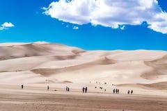 La gente che fa un'escursione nelle dune di sabbia Immagine Stock Libera da Diritti