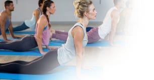 La gente che fa yoga sul pavimento in palestra Immagini Stock Libere da Diritti