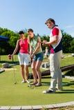 La gente che gioca golf miniatura all'aperto Fotografia Stock Libera da Diritti
