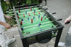La gente che gioca il primo piano di calcio-balilla all'aperto fotografie stock
