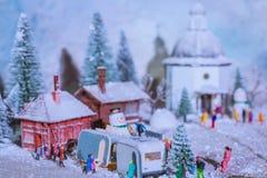 La gente che gioca nella neve vicino al caravan durante la caduta illustrazione vettoriale