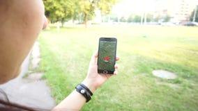 La gente che gioca Pokemon VA l'applicazione lo Smart Phone app della realtà aumentato colpo mentre prova a prendere Pokemon Zuba archivi video
