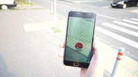 La gente che gioca Pokemon VA l'applicazione lo Smart Phone app della realtà aumentato colpo mentre prova a trovare Pokemon archivi video