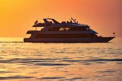 La gente che gode a bordo dell'yacht di lusso sul bakcground variopinto di tramonto immagini stock libere da diritti