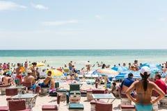 La gente che gode del caldo sulla spiaggia Fotografia Stock