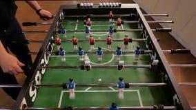 La gente che gode del gioco di calcio della tavola Chiuda su del gioco dell'estrattore a scatto di calcio-balilla archivi video