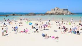 La gente che gode del rilassamento sulla spiaggia a Saint Malo video d archivio