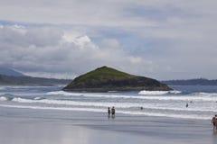 La gente che gode della spiaggia e che pratica il surfing alla roccia dell'inceneritore Rim National Park pacifico Fotografie Stock