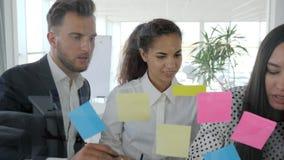 La gente che guarda agli autoadesivi variopinti, 'brainstorming', lavoratori dell'ufficio che esaminano il pianificatore della pa stock footage