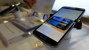 La gente che guarda prezzo da pagare con il cellulare della nota 7 della galassia di Samsung dell'esposizione stock footage