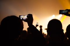 La gente che guarda un concerto e qualcuno foto e video della fucilazione con un cellulare fotografia stock