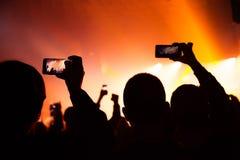 La gente che guarda un concerto e qualcuno foto e video della fucilazione con un cellulare fotografia stock libera da diritti
