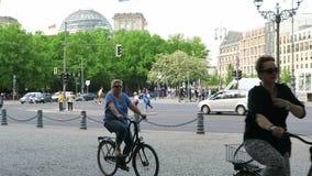 La gente che guida in bici attraverso la città di Berlino nel fondo il reichstag ed il tor di Brandenburger stock footage