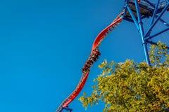 La gente che guida le montagne russe d'acciaio di torsione spaventose ad un parco di divertimenti Fotografie Stock Libere da Diritti