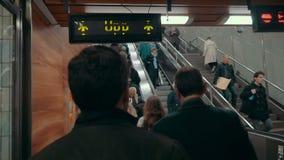 La gente che guida su e giù le scale mobili in sottopassaggio archivi video