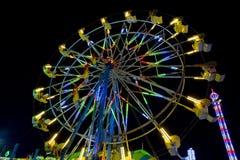 La gente che guida su Ferris Wheel alla notte Fotografia Stock Libera da Diritti