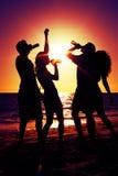 La gente che ha partito alla spiaggia con le bevande Immagine Stock