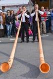La gente che indossa i vestiti tradizionali e che gioca il alphorn al KE Fotografie Stock