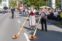 La gente che indossa i vestiti tradizionali e che gioca il alphorn all'en Fotografia Stock Libera da Diritti