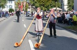La gente che indossa i vestiti tradizionali e che gioca il alphorn all'en Fotografia Stock