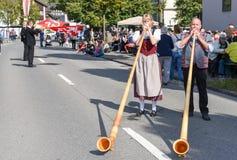 La gente che indossa i vestiti tradizionali e che gioca il alphorn all'en Immagini Stock Libere da Diritti