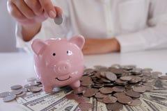 la gente che inserisce moneta in porcellino salvadanaio con le monete e soldi sopra lo scrittorio immagine stock libera da diritti