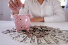 la gente che inserisce moneta in porcellino salvadanaio con le monete e soldi sopra lo scrittorio immagine stock