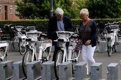 La gente che ispeziona le bici elettriche per affittare Immagine Stock