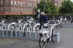 La gente che ispeziona le bici elettriche per affittare Immagini Stock Libere da Diritti