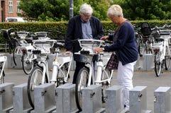 La gente che ispeziona le bici elettriche per affittare Immagine Stock Libera da Diritti