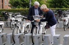 La gente che ispeziona le bici elettriche per affittare Fotografia Stock