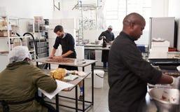 La gente che lavora insieme in una fabbrica artigianale di fabbricazione di cioccolato fotografie stock