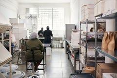 La gente che lavora in una piccola fabbrica artigianale di fabbricazione di cioccolato fotografia stock libera da diritti