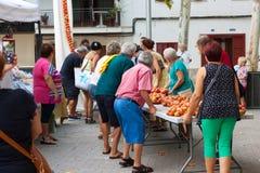 """La gente che lega insieme i pomodori per formare i mazzi d'attaccatura durante la fiera di notte """"di Ramellet """"del pomodoro in Ma fotografia stock"""