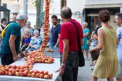 """La gente che lega insieme i pomodori per formare i mazzi d'attaccatura durante la fiera di notte """"di Ramellet """"del pomodoro in Ma fotografia stock libera da diritti"""