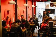 La gente che mangia la prima colazione in ristoranti indossa il permesso del ` t i loro telefoni cellulari Immagini Stock