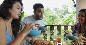 La gente che mangia le tagliatelle che parlano, gruppo Sit At Table On Terrace degli amici con la vista sulla foresta tropicale stock footage