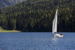 La gente che naviga un yacht su un lago della montagna Immagine Stock