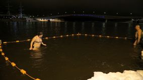 La gente che nuota in acqua fredda in fiume nell'inverno stock footage