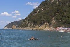 La gente che nuota nel Mar Nero su fondo naviga le rocce Villaggio Praskoveevka della stazione balneare Fotografia Stock