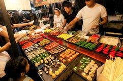 La gente che opera la scelta ai sushi si blocca con le squisitezze dei frutti di mare sul mercato di notte della città Immagini Stock