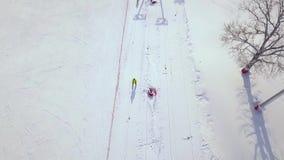 La gente che passa l'ascensore di sci sul pendio della neve nella località di soggiorno di inverno Elevatore dello sci sulla mont video d archivio
