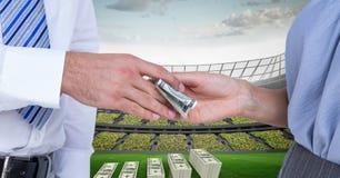La gente che passa soldi allo stadio di football americano che rappresenta corruzione Fotografie Stock Libere da Diritti