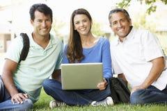 La gente che per mezzo del computer portatile all'aperto Fotografie Stock