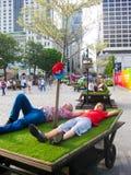 La gente che prende resto sul carretto con erba artificiale fotografia stock libera da diritti
