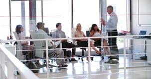 La gente che presenzia alla riunione d'affari nell'ufficio open space moderno video d archivio